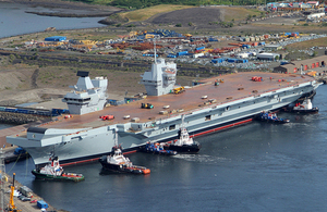 The Royal Navy's largest ever warship HMS Queen Elizabeth is gently floated out of her dock for the first time in Rosyth, Scotland.  In an operation that started earlier this week, the dry dock in Rosyth near Edinburgh was flooded for the first time to allow the 65,000 tonne aircraft carrier to float. It then took only three hours this morning to carefully manoeuvre HMS QUEEN ELIZABETH out of the dock with just two metres clearance at either side and then berth her alongside a nearby jetty. Teams will now continue to outfit the ship and steadily bring her systems to life in preparation for sea trials in 2016.  The dock she vacates will be used for final assembly of her sister ship, HMS PRINCE OF WALES, which will begin in September.  The float out of HMS QUEEN ELIZABETH comes just 13 days after the vessel was named by Her Majesty the Queen in a spectacular ceremony.  HMS QUEEN ELIZABETH and HMS PRINCE OF WALES are being delivered by the Aircraft Carrier Alliance, a unique partnership between the Ministry of Defence, BAE Systems, Babcock and Thales.